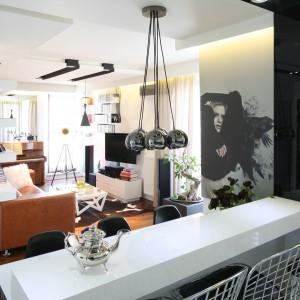 W niedużym apartamencie kuchnię otwarto na salon. Został on urządzony w modnej bieli, która wraz z lustrem zamontowanym na jednej ze ścian optycznie go powiększa. Projekt: Małgorzata Mazur. Fot. Bartosz Jarosz.
