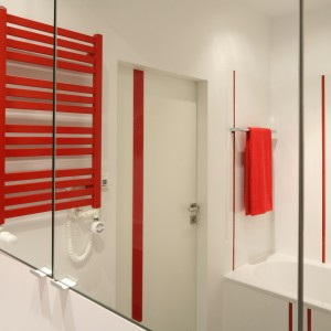 Jako element dekoracyjny zastosowano czerwone, pionowe pasy: na drzwiach, w postaci pionowych listew zdobiących okładziny. Wtórują im poziome kolektory czerwonego grzejnika. Projekt: Iza Szewc. Fot. Bartosz Jarosz.