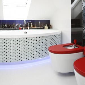 Czerwone akcenty świetnie ożywiają i dekorują łazienkę urządzoną z przewagą bieli. Efektownie wyglądają sanitariaty z czerwonymi deskami. Projekt: Marta Kilan. Fot. Bartosz Jarosz.