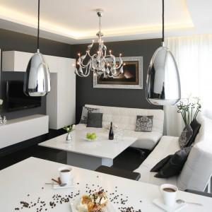 Chociaż ściany salonu zdobi ciemna szarość, białe elementy wyposażenia sprawiają, że wnętrze jest jasne. Ciemne tło znakomicie eksponuje oryginalny, pomysłowy  kształt lakierowanej meblościanki telewizyjnej. Projekt: Łukasz Sałek. Fot. Bartosz Jarosz.