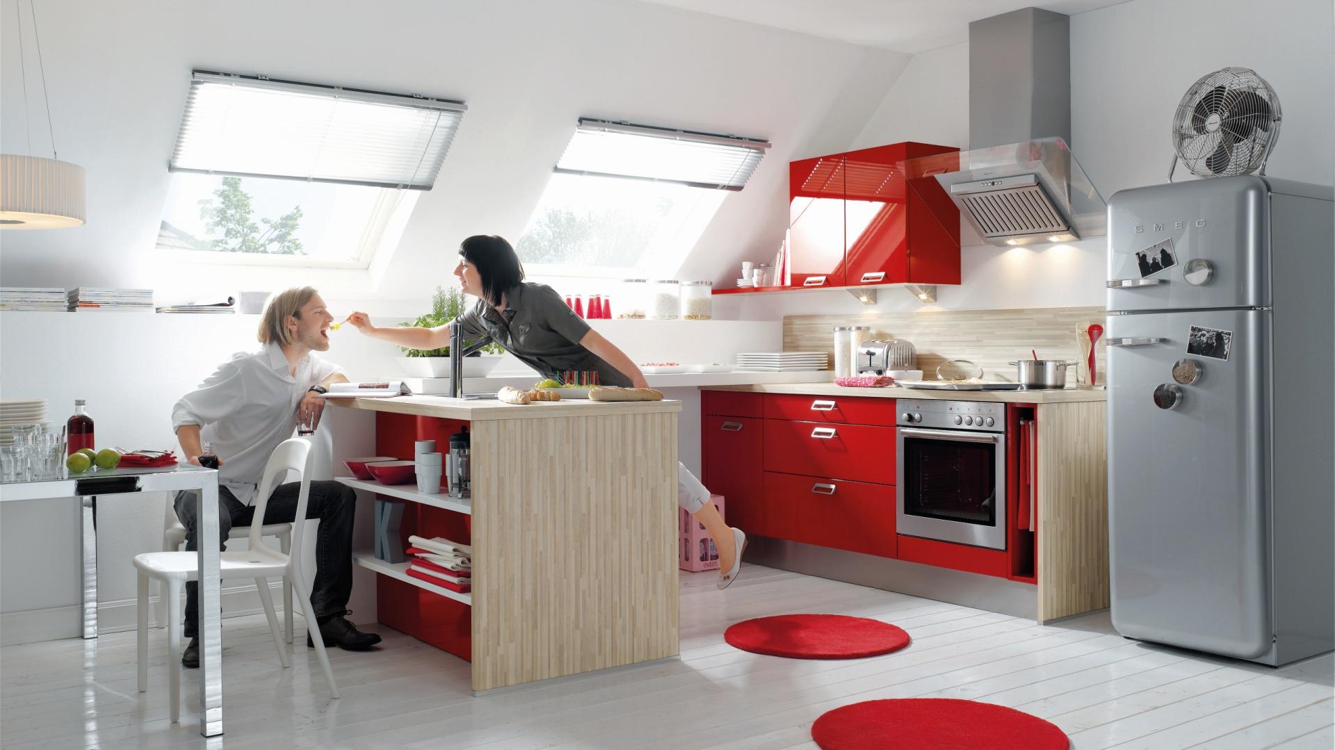 Kolor jasnego drewna połączono z elementami w mocnej, połyskującej czerwieni. W obrębie wyspy kuchennej i dolnej zabudowy drewno tonuje odważną barwę, w krótkim pasie górnych szafek - czerwień i połysk całkowicie dominują. Fot. Nobilia, kuchnia Veneto.