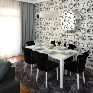 Biały, prosty w formie stół wybrano z oferty firmy Kare. Tapicerowane krzesła - z nieco bardziej ozdobnym akcentem -kupiono w sklepie B&B . . Bartosz Jarosz.