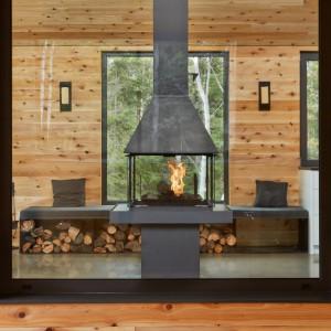 Strefę dzienną, zajmującą ostatni poziom domu, scala kominek, będący w centrum pomieszczenia. Całkowicie przeszklone palenisko, pozwala na podziwianie ognia z każdego miejsca strefy dziennej. Projekt: MU Architecture. Fot. Ulysse Lemerise Bouchard.