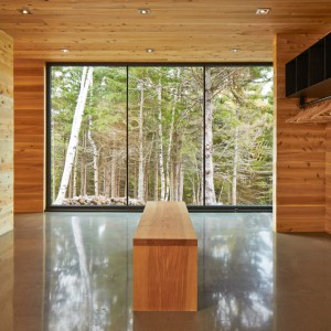 Panoramiczne przeszklenia wpuszczają do wnętrza naturalne światło, odbijające się pięknie od betonowej, połyskującej posadzki. Projekt: MU Architecture. Fot. Ulysse Lemerise Bouchard.
