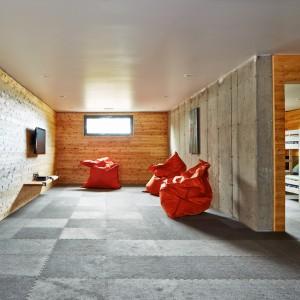 W piwnicy urządzono dużą bawialnię dla najmłodszych gości domu. Podłogę pokryto miękką wykładziną, która kolorem koresponduje z betonem na jednej ze ścian. Projekt: MU Architecture. Fot. Ulysse Lemerise Bouchard.