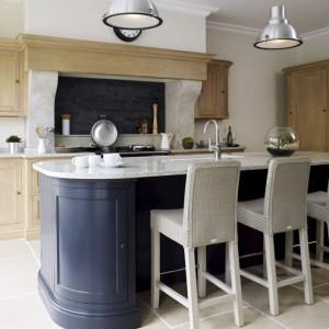 Jasny blat i wysokie krzesła uzupełniają wizualnie ciemnogranatową wyspę. Całość utrzymano w klasycznych formach. Fot. Munn Kitchens.