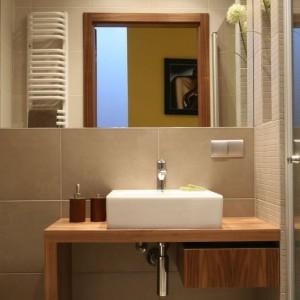 Prostokątną umywalkę umieszczono na drewnianym blacie o prostej formie. Po prawej stronie znajduje się praktyczna szuflada na niezbędne kosmetyki. Projekt: Luiza Jodłowska. Fot. Bartosz Jarosz.
