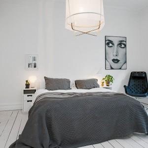 Po obu stronach łóżka umieszczono małe lampki nocne. Główne oświetlenie do sypialni dostarcza wisząca lampa z jasnym abażurem o prostej formie. Fot. Alvhem Makleri.