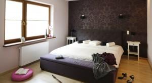 Jasne, wrzosowe odcienie ścian połączono z dekoracyjną tapetą w stylu glamour. Wyszukaneformy mebli dodają wnętrzu charakteru tworząc przytulną, elegancką sypialnię.