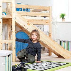 Pomysłowe łóżko na antresoli wykonane z drewna to miejsce nie tylko snu, ale i zabawy. Pod posłaniem znajduje się bowiem domek, który inspiruje do wielu ciekawych pomysłów na zabawę. Fot. Scandikids.