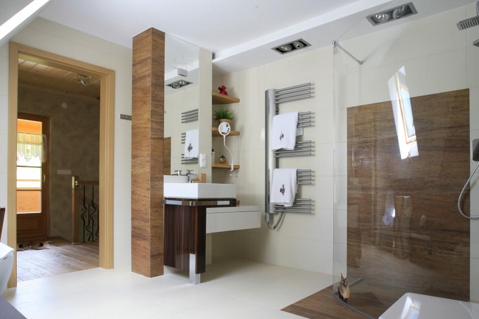 Jana, przestronna łazienka została urządzona w kolorze złamanej bieli ocieplonej rysunkiem drewna. Wszystkie okładziny zostały wykonane z płytek gresowych. Fot. Bartosz Jarosz.