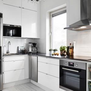 Białe meble kuchenne wieńczy ciemny blat, kontrastujący z jasnymi frontami i ścianą nad blatem. Fot. Stadshem.se/Janne Olander.