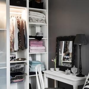 W sypialni przy łóżku usytuowano toaletkę ze stylizowaną komodą i krzesłem oraz lustrem, oprawionym w czarną, barokową ramę. Pod ścianą, za przesuwnymi drzwiczkami, udało się zmieścić garderobę na kobiece kreacje. Fot. Stadshem.se/Janne Olander.