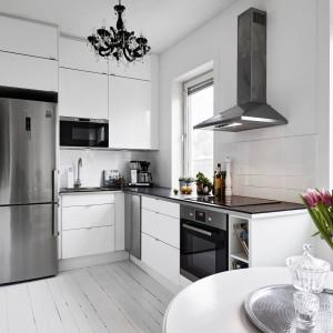 Meble kuchenne utrzymano we współczesnej stylistyce, z którą ciekawie kontrastuje dekoracyjny, czarny żyrandol. Fot. Stadshem.se/Janne Olander.