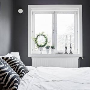 Białe ramy okien pięknie kontrastują z ciemnoszarymi ścianami w sypialni. Parapet zdobią donice z dekoracyjną roślinnością i dwa klasyczne świeczniki. Fot. Stadshem.se/Janne Olander.