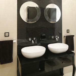 Białe umywalki o pięknych kształtach zostały doskonale wyeksponowane na czarnej szafce wykończonej w połysku. Taki duet sprawdzi się w każdej łazience. Projekt: Michał Mikołajczak. Fot. Bartosz Jarosz.