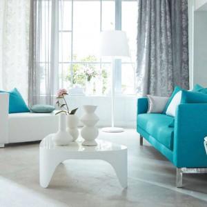 Wnętrze w stonowanej szarości i bieli skutecznie ożywia niewielka, turkusowa sofa. Aranżację dopełniają poduszki dekoracyjne w kolorze tapicerki. Tkaniny z kolekcji Prisme marki Camengo. Fot. Camengo.