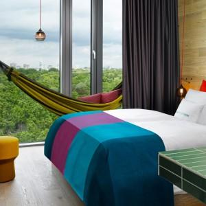 Wnętrza hotelu w Berlinie. Naturalne drewno w jasnym odcieniu współgra z kolorowymi tkaninami. Obok panoramicznego okna z widokiem na berlińskie zoo umieszczono wygodny hamak. Fot. 25 hours Hotels.
