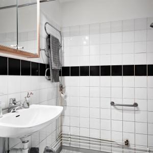 Łazienkę, podobnie jak resztę mieszkania, utrzymano w czerni i bieli. Aranżację ociepla drewniana szafka nad umywalką z drzwiczkami, pokrytymi taflą lustra. Fot. Stadshem.se/Janne Olander.