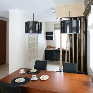 Dwie lampy z czarnymi, połyskującymi kloszami nadają elegancki charakter jadalni, komponując się z czarnymi krzesłami. Projekt: Karolina Łuczyńska. Fot. Bartosz Jarosz.