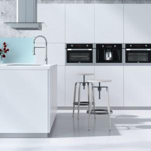 Biała, nowoczesna kuchnia z wysoką zabudową w białym kolorze. Sprzęty AGD umieszczono w jednym, poziomym rzędzie, w oddzielnych słupkach zabudowy. Ciemne urządzenia odznaczają się na tle białych frontów. Fot. Teka.