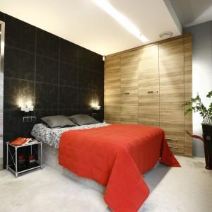 Najmocniejszym elementem w tej sypialni jest ściana za łóżkiem. W tym wypadku proste w formie oświetlenie pasuje doskonale. Projekt: Liliana Masewicz-Kowalska. Fot. Bartosz Jarosz.