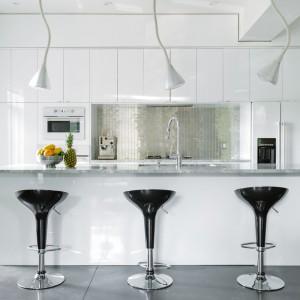 Kuchnia zachwyca nowoczesnym wystrojem. Jej przestrzeń tworzy wysoka zabudowa i długa wyspa, funkcjonująca jako bar. Nad nim wiszą efektowne, designerskie, białe lampy. Ścianę nad powierzchnią roboczą wykończono piękną, srebrną mozaiką. Z reżimu jasnych barw wyłamują się czarne hokery. Projekt: MU Architecture. Fot. Ulysse Lemerise Bouchard.