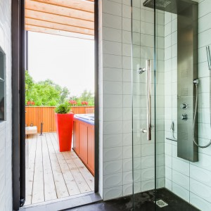 Do jacuzzi na tarasie można przejść przez strefę prysznica w łazience. Projekt: MU Architecture. Fot. Ulysse Lemerise Bouchard.