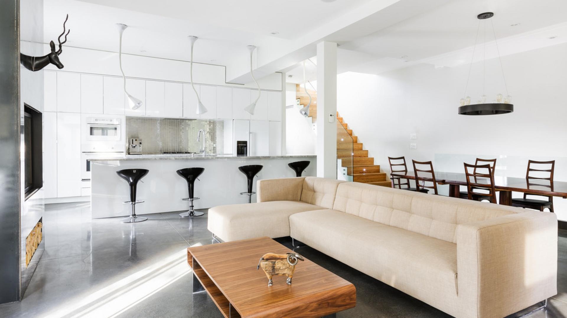 Na pierwszym piętrze mieszkania urządzono obszerną strefę dzienną. Objęła ona kuchnię z dużym, długim barem, dużą jadalnię i kącik salonowy. Projekt: MU Architecture. Fot. Ulysse Lemerise Bouchard.
