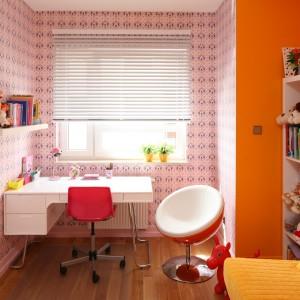 W najjaśniejszym miejscu pokoju, czyli przy oknie, zorganizowano strefę nauki. Efektownie wydzielono ją wzorzystą tapetą w różowym kolorze. Projekt: Dorota Szafrańska. Fot. Bartosz Jarosz.