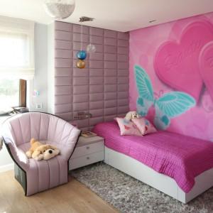 Dziewczęcy ton aranżacji nadaje spektakularna fototapeta, zdobiąca całą powierzchnię ściany. Różowe serca i pastelowe motyle na tle motywów roślinnych gwarantują dziecku kolorowe sny, lecz także ożywiają jasny wystrój przestronnego pokoju. Projekt: Agnieszka Hajdas-Obajtek. Fot. Bartosz Jarosz.