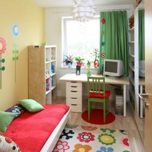 W najjaśniejszym miejscu pokoju ustawiono jasne biurko oraz zielone, proste krzesło wyścielone czerwoną poduszką. W słoneczne dni nadmiar światła zatrzyma zasłona w kolorze świeżej trawy, którą zdobią aplikacje identyczne jak kwiaty na dywanie. Projekt: Marta Kruk. Fot. Bartosz Jarosz.