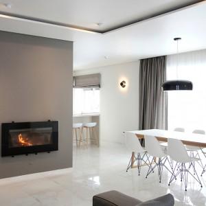 Funkcję łącznika pomiędzy salonem i kuchnią pełni jadalnia. Nowoczesny stół i krzesła w stylu eamesowskim utrzymano w jasnych kolorach, kontrastujących z oświetleniem w jadalni. Projekt: Ramunas Manikas, Valdas Kontrimas. Fot. Ramunas Manikas.