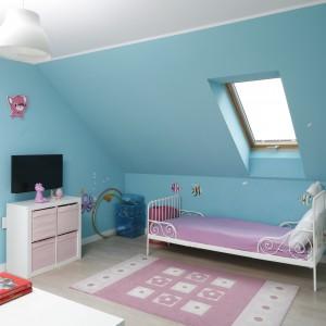 Subtelne, kute łóżko pomalowane na biało ustawiono pod skosem, przy oknie dachowym. Błękitny kolor ścian stapia się więc z barwą nieba, widocznego przez niewielkie okno. Projekt: Beata Ignasiak-Wasik. Fot. Bartosz Jarosz.