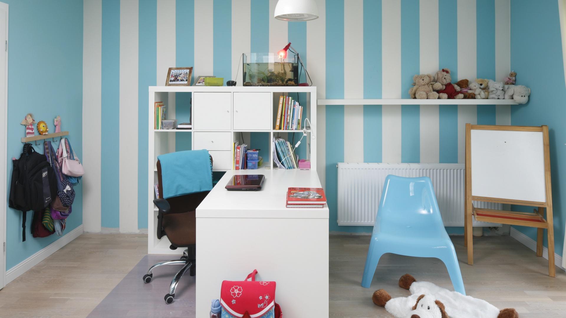 Biało-niebieskie pasy na ścianie obok biurka wyznaczają przestrzeń nauki, a także sprawiają, że pomieszczenie na poddaszu wydaje się wyższe. Projekt: Beata Ignasiak-Wasik. Fot. Bartosz Jarosz.