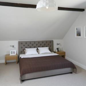 Sypialnia urządzona jest w jasnej, spokojnej kolorystyce. Mocniejszym akcentem jest łóżko z pięknym, pikowanym zagłówkiem, które jednak doskonale wpisuje się w całą aranżację. Projekt: Kamila Paszkiewicz. Fot. Bartosz Jarosz.