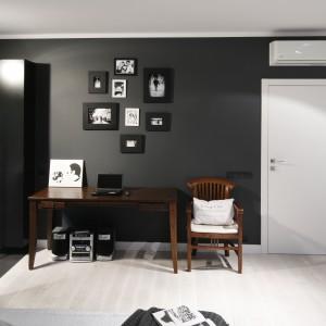 Przestrzeń sypialni i czarnej łazienki spaja wizualnie ciemna ściana. Przy granicy pomieszczeń zlokalizowano stylizowany drewniany stół, nad którym urządzono kącik z galerią zdjęć, tak jak większość pomieszczenia - czarno-białą. Projekt: Maciejka Peszyńska-Drews. Fot. Bartosz Jarosz.