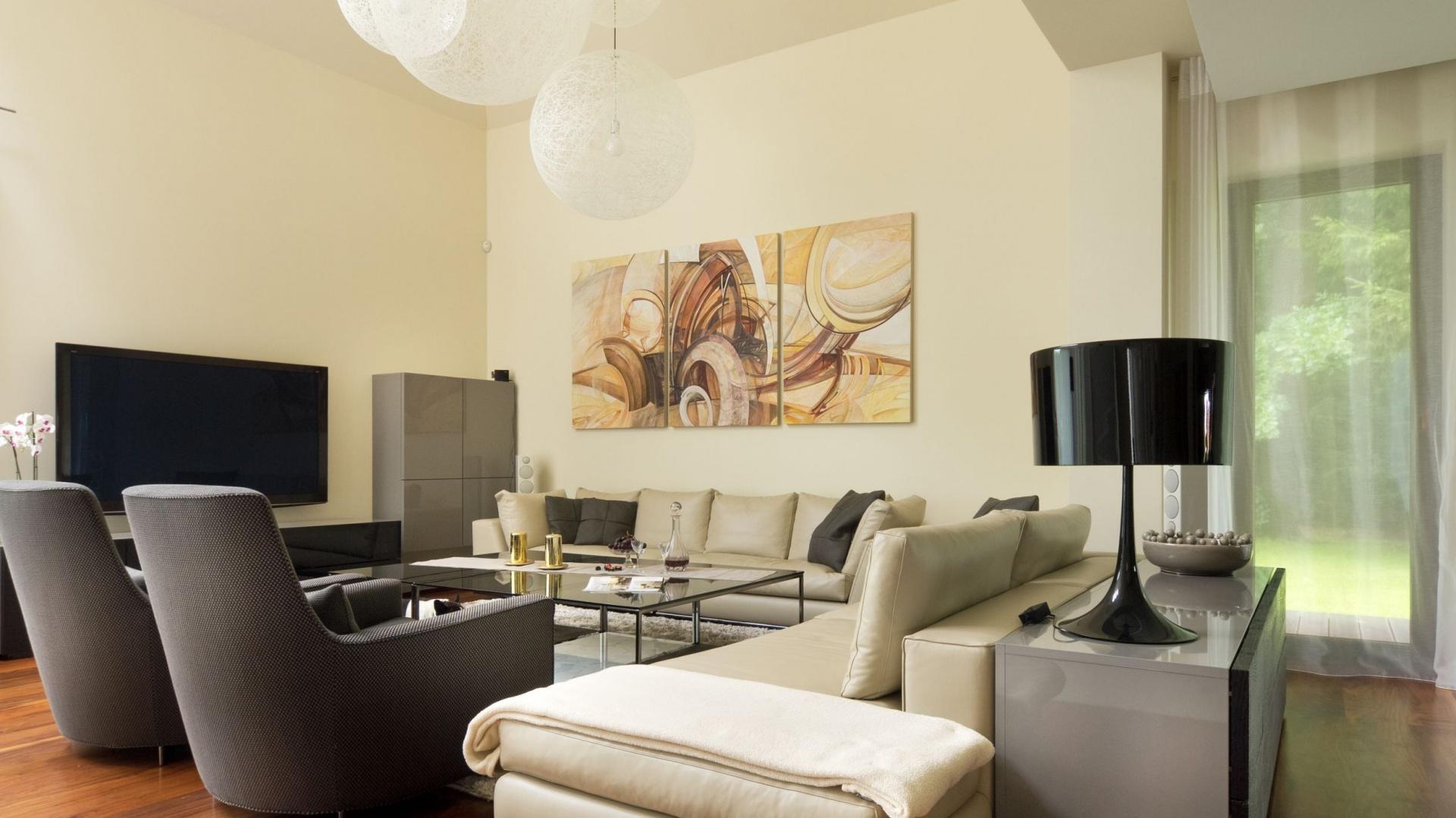 Nowoczesną formę mebli wypoczynkowych ociepla kolor: ciepły krem narożnika oraz czekoladowy brąz foteli. Ciekawym akcentem jest współczesny tryptyk, który zdobi beżową ścianę. Projekt: Tomasz Tubisz. Fot. Przemysław Andruk.