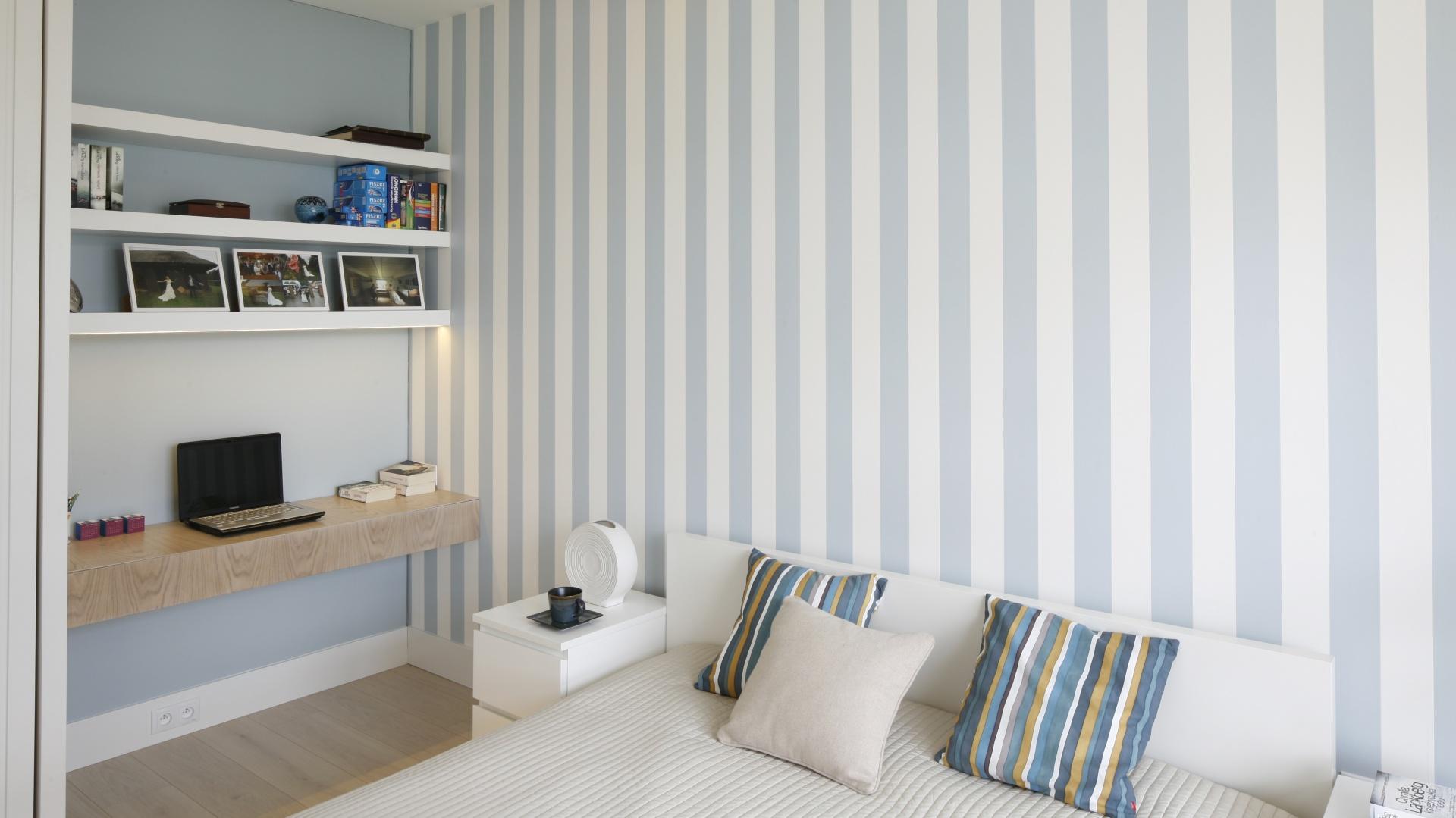 Na ścianie za łóżkiem umieszczono tapetę w pionowe pasy. Błękit w połączeniu z bielą i jasnym drewnem tworzy przytulne wnętrze. Fot. Bartosz Jarosz.