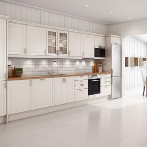 Meble kuchenne w kolorze złamanej bieli mają delikatnie zdobną, klasycyzującą formę. Praktyczne, pojemne półki nad blatem skrywają praktyczne kuchenne akcesoria, widoczne przez delikatne przeszklenia, dodające zabudowie lekkości. Fot. Sigdal, kuchnia Bello.