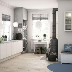 Jasnoszare ściany, drewniana podłoga, kominek w postaci wolno stojącej kozy i biłe meble kuchenne. Piękna, delikatnie rustykalna aranżacja skandynawskiej kuchni. Fot. HTH, kuchnia KT10.