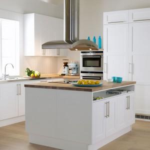 Piękna, jasna kuchnia, w której białe meble kuchenne ocieplono drewnianym blatem w ciepłym, miodowym odcieniu i drewnianą podłogą w taki samym kolorze. Fot. Ballingslov, linia Studio.