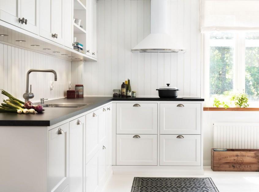 Drewno w białym wydaniu. Taką aranżację kuchni proponuje szwedzka firma Ballingslov. A kto jak nie Skandynawowie wie najlepiej jak urządzić kuchnię skandynawską? Białe meble kuchenne z ciemnobrązowym, drewnianym blatem ustawiono na tle ściany, pokrytej pionową deską, pomalowaną na biały kolor. Fot. Ballingslov, linia Gastro.
