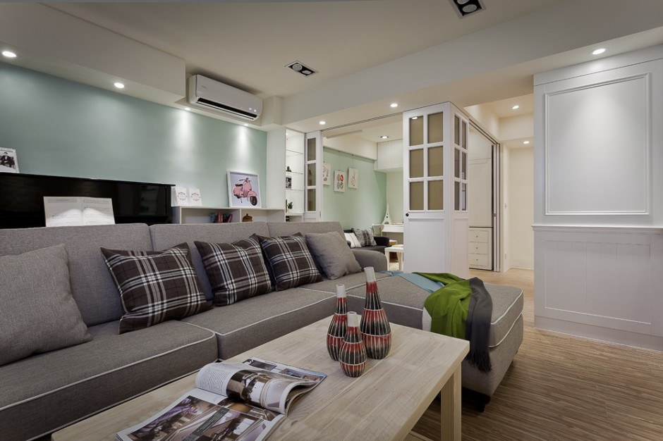 W salonie dominują delikatne, jasne kolory. Dominację beżów i bieli przełamano ścianą w kolorze wymytej zieleni. Projekt i zdjęcia: Moon Refined Design.