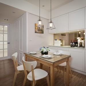 Biała, lekko frezowana zabudowa nadaje przestrzeni jadalni romantyczny charakter. Drewniana podłoga i stół ocieplają białą przestrzeń. Projekt i zdjęcia: Moon Refined Design.