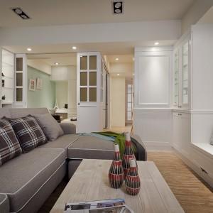 Salon sąsiaduje z jadalnią i kącikiem, który może pełnić rolę gabinetu. Przestrzeń obu funkcji spaja jasnozielona ściana. Lekkości wnętrzu dodaje biała zabudowa, a domowy klimat we wnętrzu buduje kamień dekoracyjny na ścianie. Projekt i zdjęcia: Moon Refined Design.
