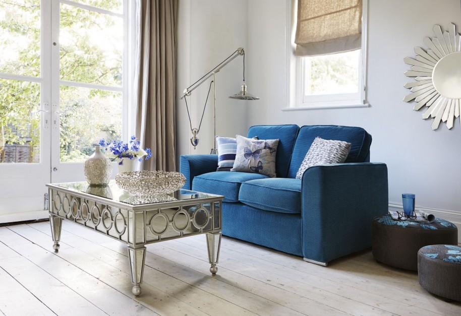 Dekoracyjny, witrażowy stolik kawowy oraz dwuosobowa sofa w intensywnym, niebieskim kolorze to recepta na subtelną, kobiecą strefę wypoczynkową. Fot. Furniture Village.