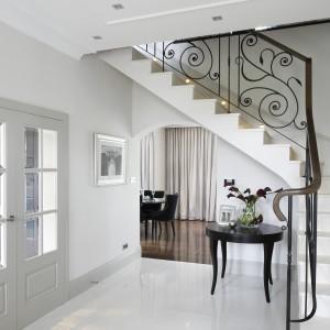 W holu wzrok przyciąga stylizowany stolik i efektowna, ozdobna balustrada schodów. Projekt: Alexander James Interiors. Fot. Bartosz Jarosz.