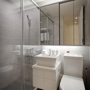 Łazienkę zdominowały modne szarości i nowoczesne kształty. W niewielką przestrzeń sprawnie wpasowano dużą strefę prysznica, schowaną za prostym przeszkleniem, umywalka znajduje się pomiędzy wc, a kabiną, a ścianę pokrywa bezramowe lustro, optycznie powiększające przestrzeń. Projekt i zdjęcia: Moon Refined Design.