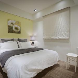 Dominację bieli i szarości w sypialni przełamano ścianą w żółtym kolorze. Jego tonacja wpisuje się jednak w ziemiste odcienie całego mieszkania. Projekt i zdjęcia: Moon Refined Design.